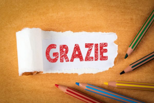 Word Grazie Means Thank You. Colored pencils on an orange background. Text under torn paper